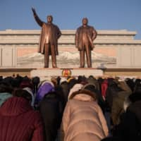 People bow before the statues of late North Korean leaders Kim Il Sung and Kim Jong Il on Mansu Hill, to mark the 72nd anniversary of the founding of Korean People's Army in Pyongyang Saturday. | AFP-JIJI