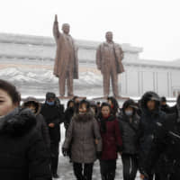 North Koreans visit the statues of the late leaders Kim Il Sung (left) and Kim Jong Il on Mansu Hill in Pyongyang on Sunday to commemorate the 78th birthday of Kim Jong Il. | AP