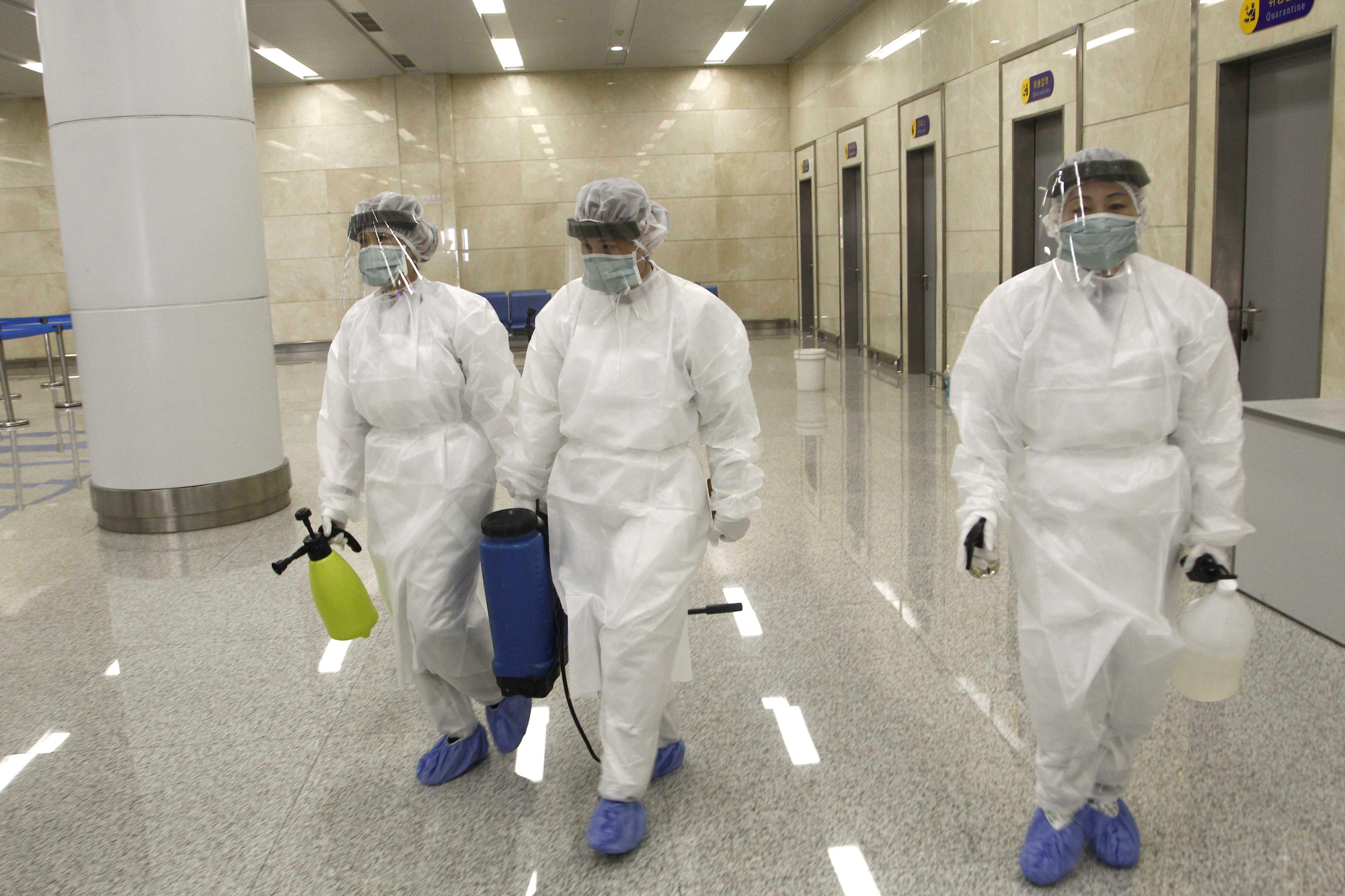 State Commission of Quality Management staff armed with protective gear and disinfectant prepare to check the health of travelers arriving from abroad at the Pyongyang Airport in Pyongyang Saturday.   AP