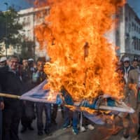 Moroccans burn the Israeli flag during a demonstration against the U.S. Middle East peace plan in the capital Rabat on Sunday.   AFP-JIJI