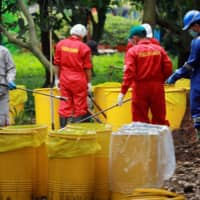 Officials from the National Nuclear Energy Agency of Indonesia (BATAN) and Nuclear Energy Regulatory Agency (BAPETEN) decontaminate soil that was exposed to radioactive waste in the residential area of Batan Indah, Tangerang, near Jakarta Monday. | ANTARA FOTO / MUHAMMAD IQBAL / VIA REUTERS