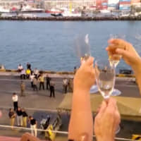 Passengers cheer and clink wine glasses as the MS Westerdam cruise ship docks at port in Sihanoukville, Cambodia, Thursday in this still image obtained from social media video. | ANGELA JONES / VIA REUTERS