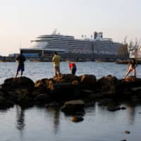 The MS Westerdam cruise ship is moored Thursday in Sihanoukville, Cambodia, where it has been granted permission to dock following nearly two weeks at sea after being turned away by five countries over coronavirus fears. | REUTERS
