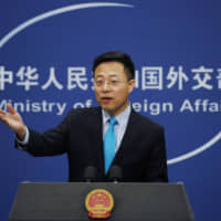 Chinese Foreign Ministry spokesman Zhao Lijian gestures as he speaks during a daily briefing at the Ministry of Foreign Affairs office in Beijing Monday. China's foreign ministry on Monday said it didn't matter that three expelled journalists had nothing to do with a Wall Street Journal editorial that Beijing deemed racist, and called on the paper to apologize. | AP