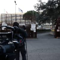 Journalists work outside a restricted entrance of the criminal court of Rome Wednesday during the trial of two Americans accused of killing a police officer in Rome last year. The two U.S. students appeared on the first day of their trial over the fatal stabbing last year of a policeman during a botched drug bust. | AFP-JIJI