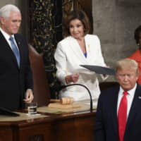 U.S. President Donald Trump turns after handing copies of his speech to House Speaker Nancy Pelosi and Vice President Mike Pence as he prepares to deliver his State of the Union address to a joint session of Congress on Tuesday. | AP