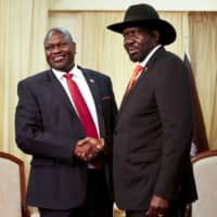 South Sudan's ex-vice president and former rebel leader, Riek Machar (left), meets with South Sudan President Salva Kiir at the presidential office in Juba last year. Kiir and Machar agreed Thursday to form a unity government Saturday, a long-delayed step toward ending six years of war. | AFP-JIJI
