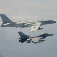 A Chinese H-6 bomber (left) flies near a Taiwan F-16 fighter jet on Monday. | TAIWAN DEFENSE MINISTRY / VIA REUTERS