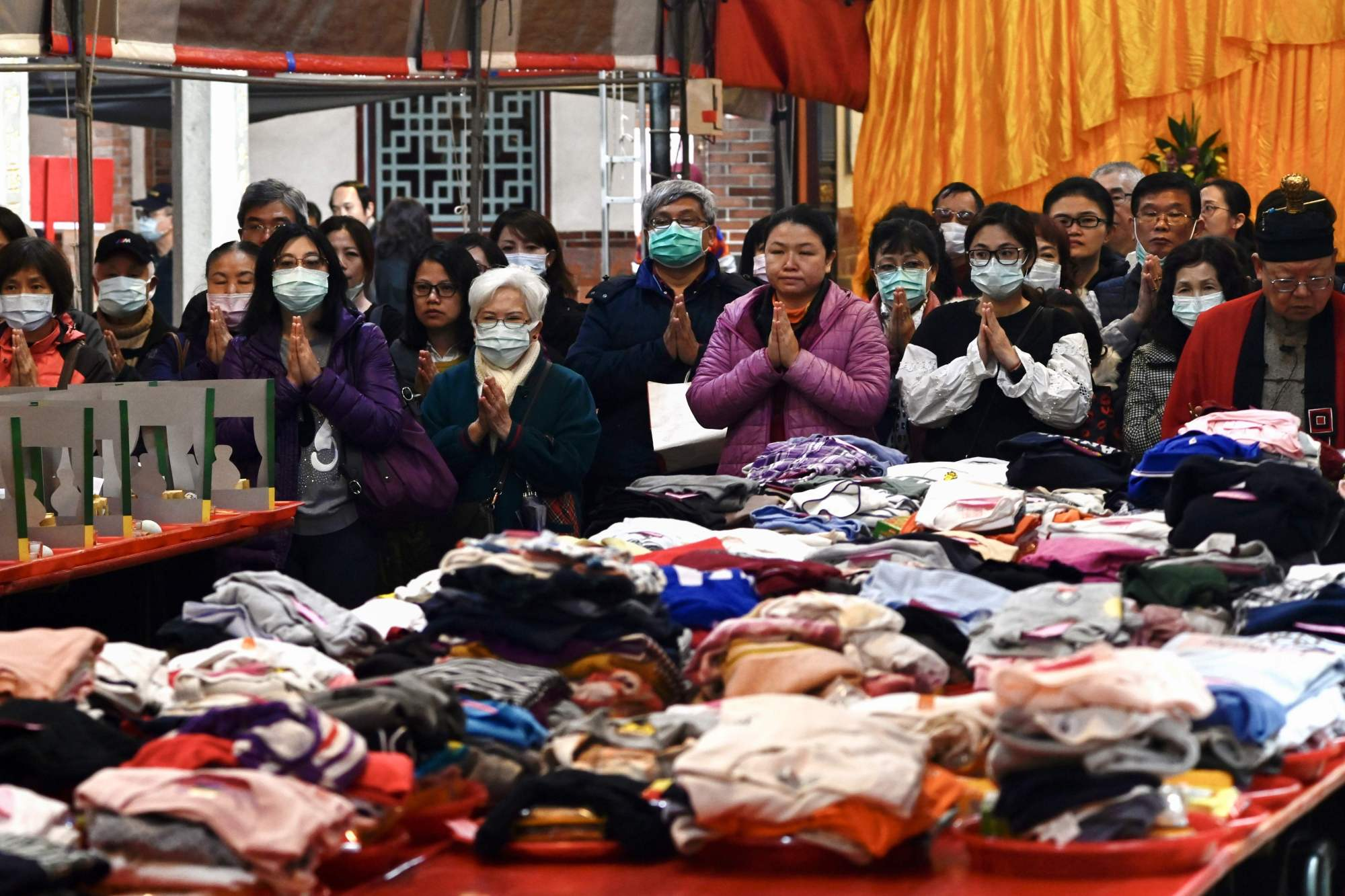 People wearing protective masks pray beside their clothes laid out on a table at a Taoist Baoan temple in Taipei on Tuesday. | AFP-JIJI
