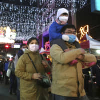 People in Taiwan wear protective face masks as they view lanterns on display for the Lunar New Year in Taipei on Feb. 9. | AP