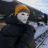 A supporter of the indigenous Wet'suwet'en Nation wears a mask as they join others occupying railway tracks as part of a protest against British Columbia's Coastal GasLink pipeline, in Toronto on Saturday. | REUTERS