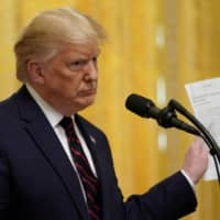 U.S. President Donald Trump responds to a question about Ukraine and the whistleblower report while holding a news story from the New York Times during a joint news conference with Finland President Sauli Niinisto at the White House in Washington last fall. | REUTERS
