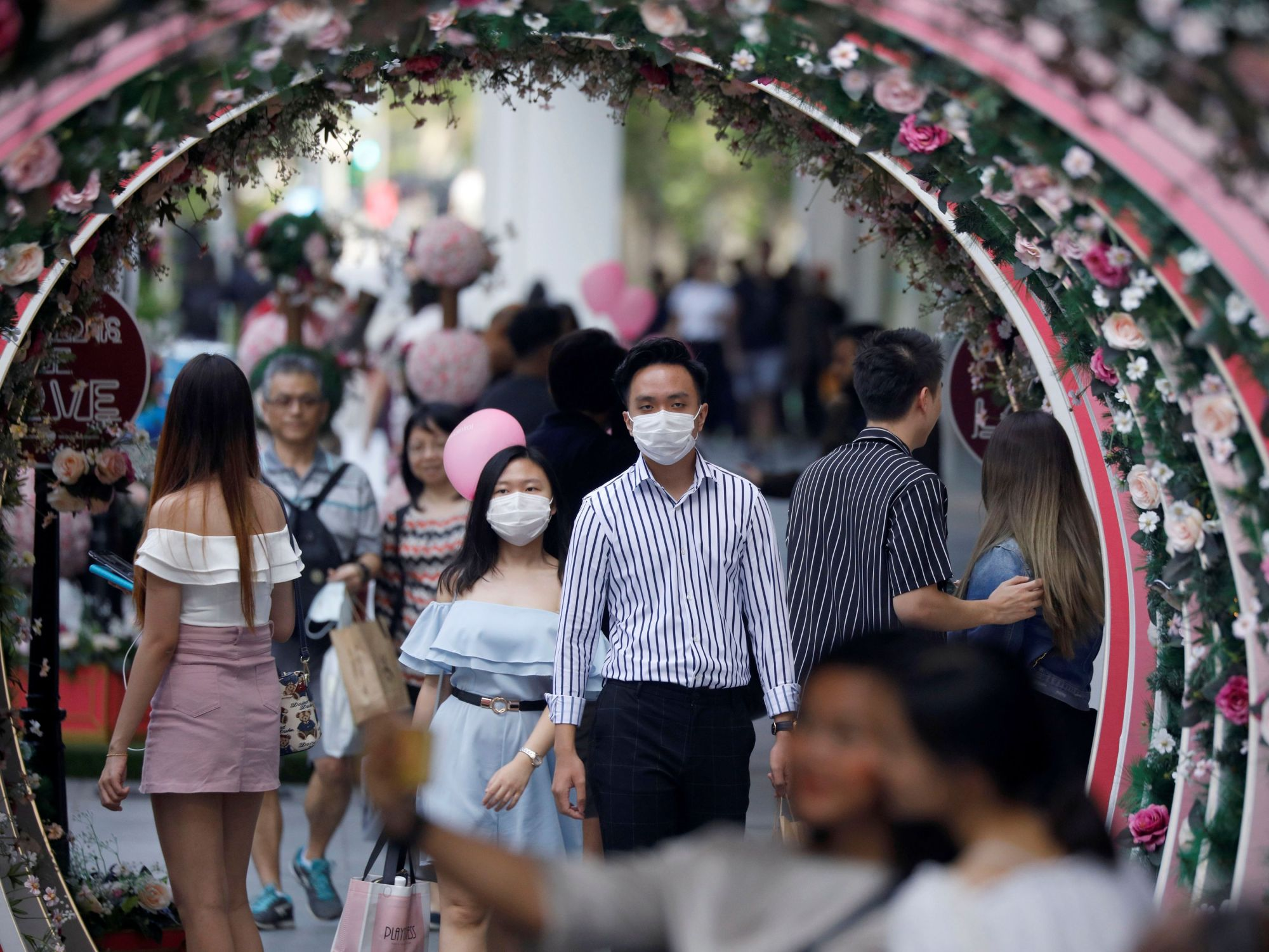 A masked couple celebrate Valentine's Day at Orchard Road in Singapore on Friday. | REUTERS