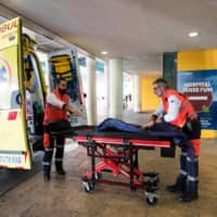 Two men ready an ambulance outside the Son Espases University Hospital in Palma de Mallorca where a British man has been diagnosed with coronavirus, on Sunday. | AFP-JIJI