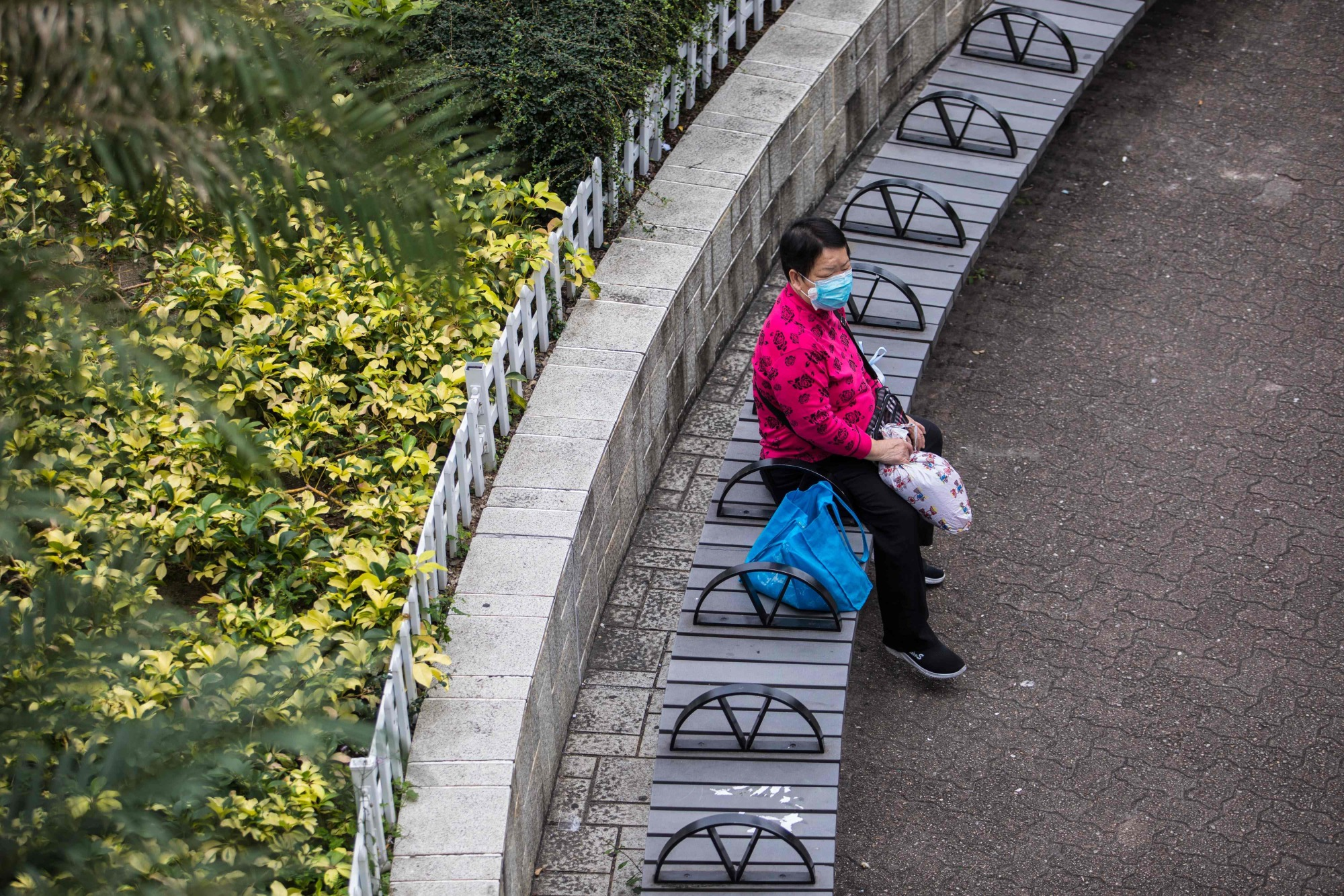 A woman wearing a protective face mask sits in a park in Hong Kong on Sunday as a preventative measure after the coronavirus outbreak that began in Wuhan, China. The previously unknown virus has caused alarm because of its similarity to SARS, the severe acute respiratory syndrome that killed hundreds across mainland China and Hong Kong from 2002 to 2003. | AFP-JIJI