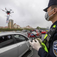 A police officer operates a drone near an expressway toll station in Shenzhen, in southern China's Guangdong Province, on Tuesday.   AP