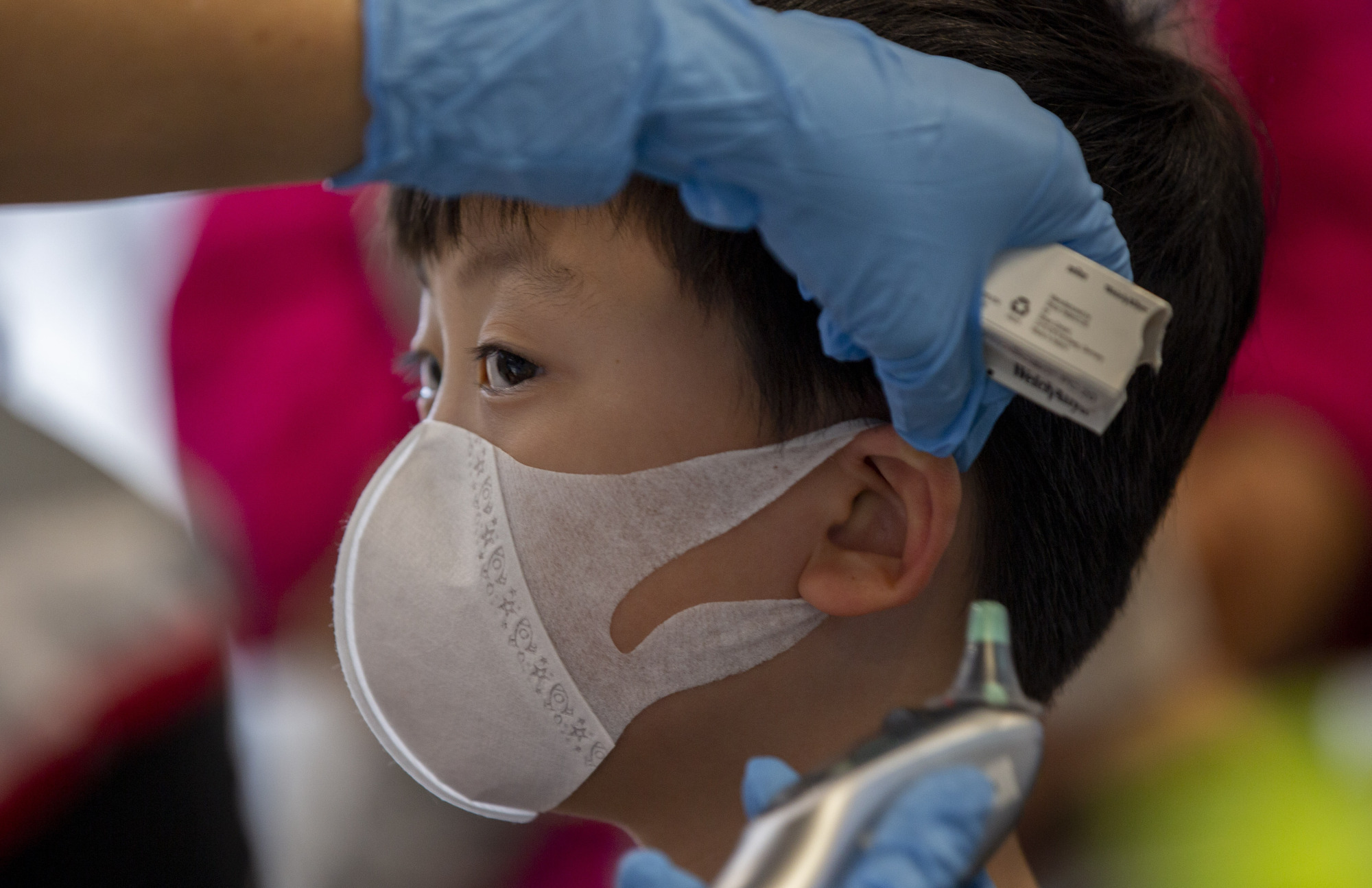 A health worker checks the temperature of tourist from Wuhan, China, as he waits for a charter flight back to the Chinese city at the Suvarnabhumi Airport in Bangkok on Friday.   AP
