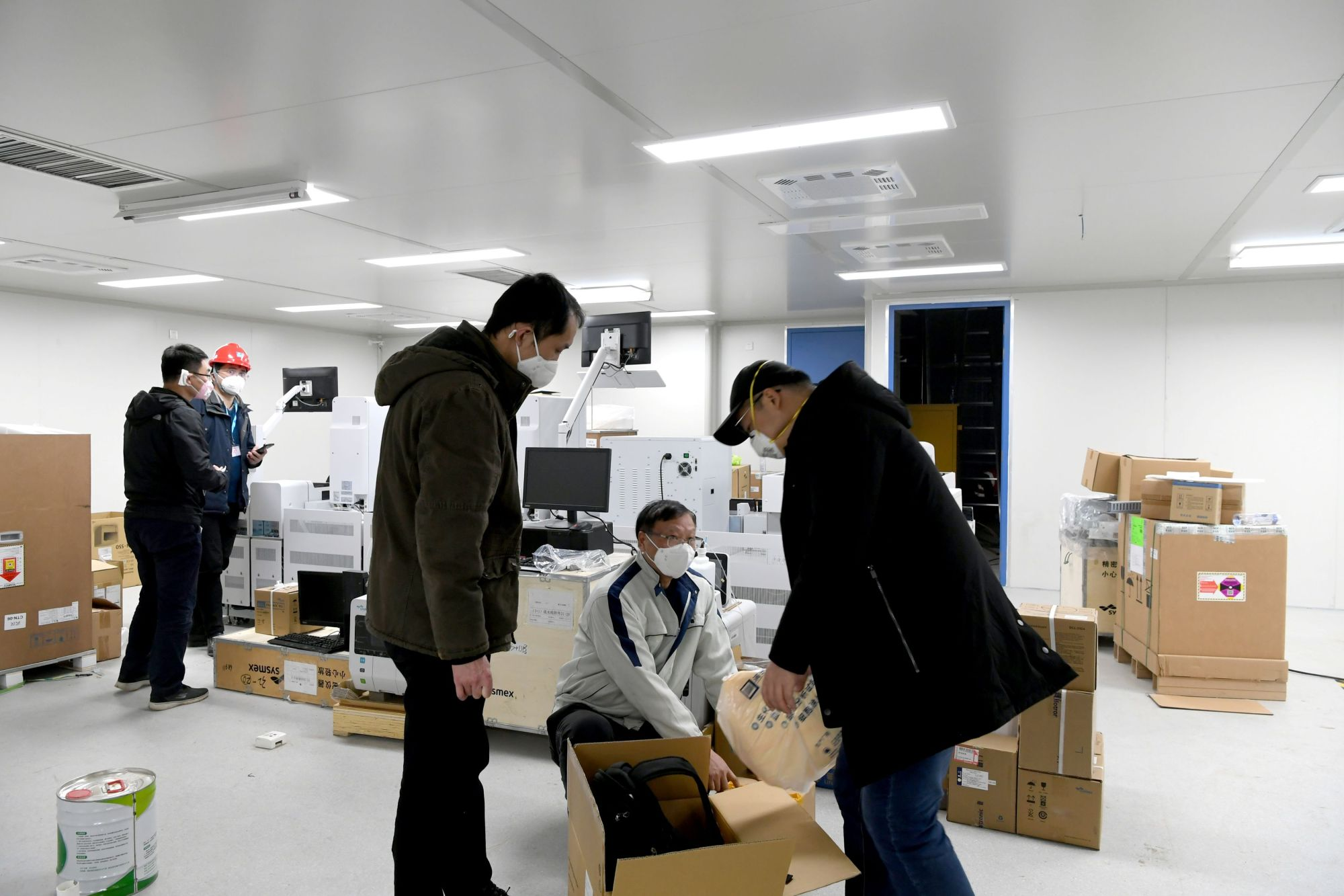Workers set up medical equipment at the Leishenshan Hospital, a facility for treating patients of the new coronavirus that is under construction, in Wuhan, China, on Wednesday.   REUTERS
