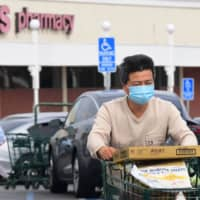 A man wears a facemask while pushing his shopping cart in Alhambra, California, Thursday. | AFP-JIJI