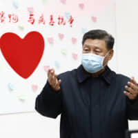 Chinese leader Xi Jinping gestures near a sign that says 'Race against time, Fight the Virus' during an inspection of the center for disease control and prevention of Chaoyang District in Beijing on Feb. 10. | XINHUA / VIA AP