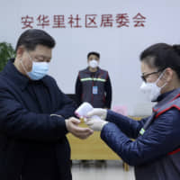 Chinese President Xi Jinping, wearing a protective face mask, receives a temperature check as he visits a community health center in Beijing on Monday. | XINHUA / VIA AP