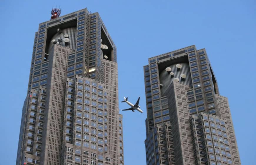 An airplane flies above the Tokyo Metropolitan Government building on Sunday to test a new low-altitude route set to be introduced in March. | KYODO