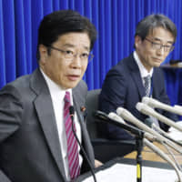 Health minister Katsunobu Kato (left) attends a news conference at the ministry on Feb. 16 along with Takaji Wakita, head of the National Institute of Infectious Diseases. | KYODO