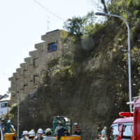 Rescuers on the scene of a landslide that killed an 18-year-old woman on Wednesday | KYODO