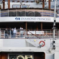 Crew members are seen aboard the Diamond Princess cruise ship at the Daikoku Pier Cruise Terminal in the port of Yokohama on Monday. Hundreds of crew members were to begin disembarking on Thursday. | AFP-JIJI