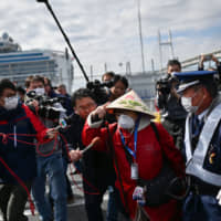 A passenger leaves a port in Yokohama on Wednesday after disembarking the Diamond Princess cruise ship. | AFP-JIJI