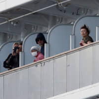 Passengers look out from their cabins as the cruise ship Diamond Princess, where 10 people on the ship tested positive for coronavirus Thursday, arrives at Daikoku Pier Cruise Terminal in Yokohama the same day. | REUTERS