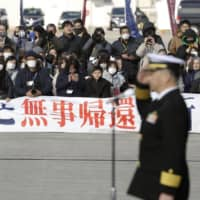 Maritime Self-Defense Force personnel with the Takanami destroyer are seen off by supporters at its base in Yokosuka, Kanagawa Prefecture, ahead of the warship's departure Sunday for the Middle East as part of the MSDF's first long-term intelligence-gathering mission abroad.   KYODO