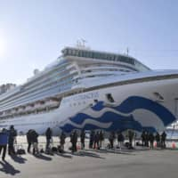 Media teams gaze at the Diamond Princess after it docked in Yokohama port on Sunday. Some of the passengers and crew have tested positive for the new coronavirus. | KYODO