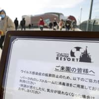 A sign is put up near a train station close to Tokyo Disneyland asking visitors to use hand sanitizer in a photo taken on Feb. 3. The theme park will be closed from Saturday amid the outbreak of COVID-19 infections. | KYODO