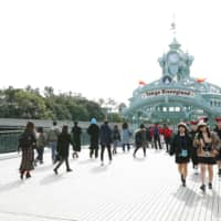 People walk toward Tokyo Disneyland in Urayasu, Chiba Prefecture, on Friday. The park's operator announced the same day that it will be closed from Saturday through March 15 amid a rise in COVID-19 infections. | KYODO