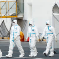 Workers wearing protective suits near the cruise ship Diamond Princess in Yokohama | REUTERS
