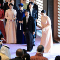 Emperor Naruhito and Empress Masako acknowledge tea party guests at the Imperial Palace on Sunday. The party was part of a series of events organized to celebrate the emperor's 60th birthday.   POOL / VIA KYODO