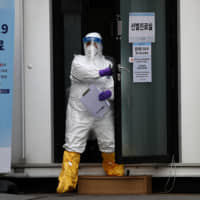 A medical professional is seen Monday at a preliminary testing facility at the National Medical Center in Seoul, where patients suspected of having COVID-19 are being assessed. | GETTY IMAGES