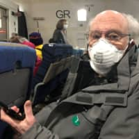 Phil Courter, a U.S. passenger on board the Diamond Princess cruise ship, wears a face mask on a chartered evacuation aircraft to fly back to the United States, at Haneda airport in Tokyo Monday.   COURTESY OF PHILIP AND GAY COURTER / VIA REUTERS