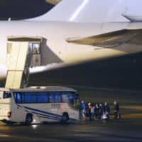 People who evacuated from the Diamond Princess cruise ship after an outbreak of COVID-19 board a U.S. government-chartered plane at Haneda airport in Tokyo on Monday.   ??