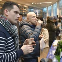 Visitors to the Paris Japan Cultural Center taste sake at an event featuring sake and food from Fukushima Prefecture on Jan. 23. | KYODO