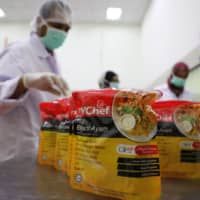 Workers arrange food packages at the Mychef halal food factory in Kuala Lumpur. | REUTERS