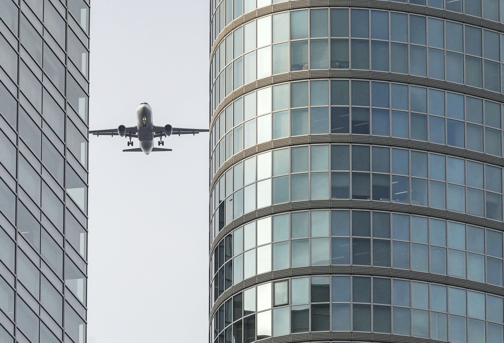 A plane flies over central Tokyo on Feb. 3 in a test of new flight paths bound for Haneda Airport.   KYODO