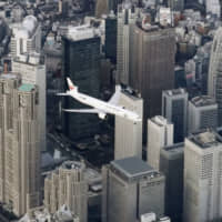 A Japan Airlines jet flies over the Shinjuku area in Tokyo to test a new low-altitude flight path to Haneda Airport on Feb. 2. | KYODO