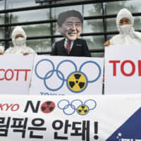 People in protective gear gather in front of the Japanese Embassy in Seoul on Aug. 7, 2019, calling for a boycott of the 2020 Tokyo Olympics, citing the need to protect athletes from exposure to radioactive substances released in the wake of the 2011 Fukushima nuclear crisis. | KYODO