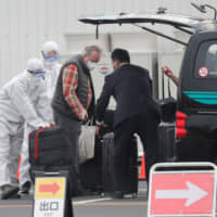 A passenger's luggage is loaded into a vehicle after he disembarked from the coronavirus-hit Diamond Princess cruise ship in Yokohama on Thursday. | REUTERS