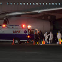 Philippine Department of Foreign Affairs and Department of Health members wear protective suits as they assist Filipinos from the Diamond Princess cruise ship as they arrive at the Clark Airbase, in Pampanga, Philippines, early Wednesday. | DFA / VIA AP