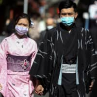 Tourists wearing kimono and protective masks visit Sensoji Temple in the Asakusa district of Tokyo on Tuesday. | REUTERS