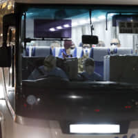A bus carrying foreign passengers from the quarantined Diamond Princess cruise ship leaves Yokohama port on Friday. Israel's health ministry said the same day that an Israeli woman who was a passenger aboard the ship tested positive upon return to her home country.   AP