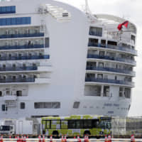 A bus carrying passengers from the quarantined Diamond Princess cruise ship leaves the port of Yokohama on Wednesday. | AP